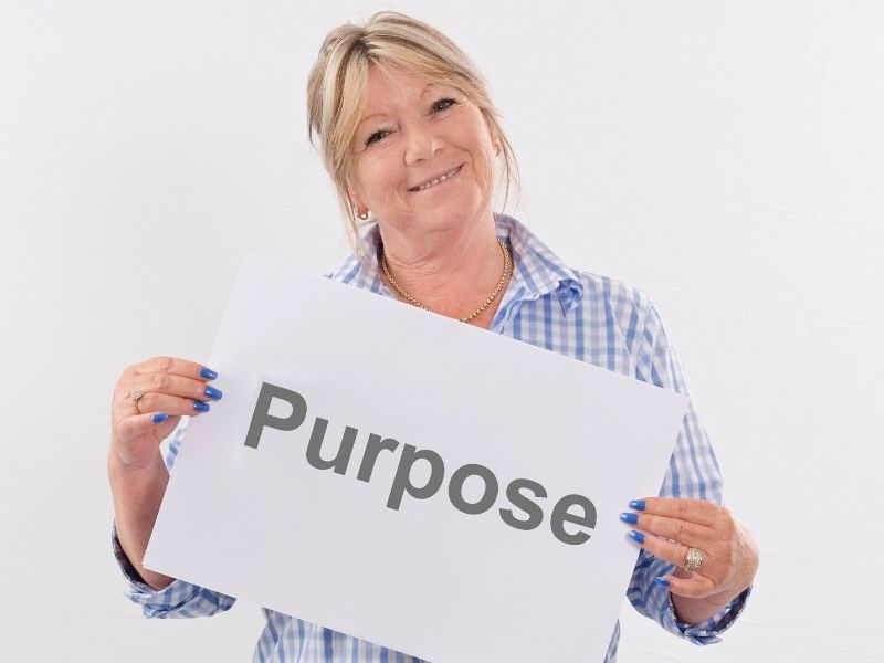 Woman holding a paper with the word purpose on it
