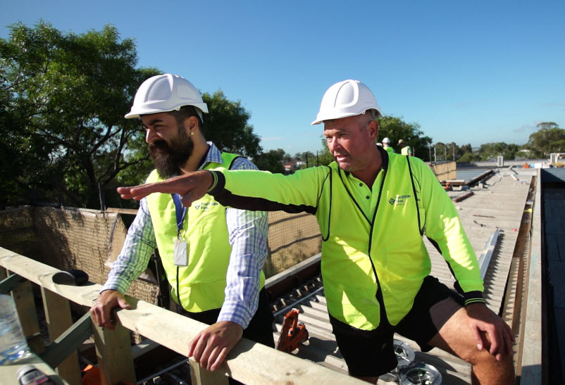 Men working on roof construction site   Facilities First