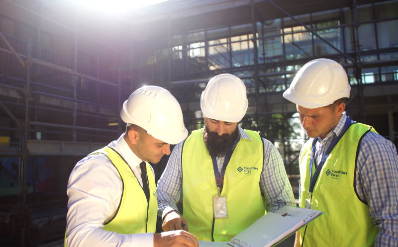 Men on construction site looking at paperwork | Facilities First