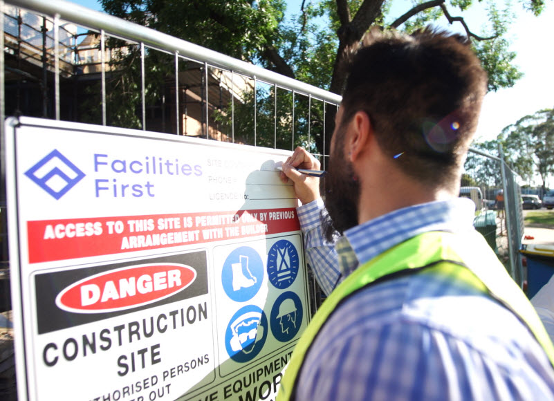 Man writing on the building permit of the construction site