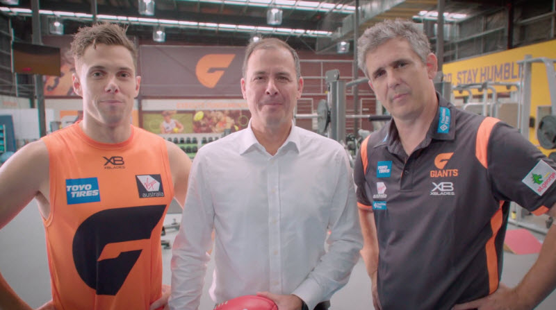 Three men inside a sports gym looking at the camera