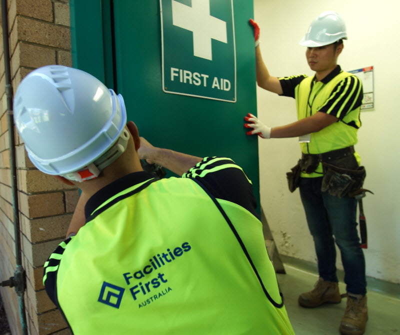 Men fixing a door with a first aid sign