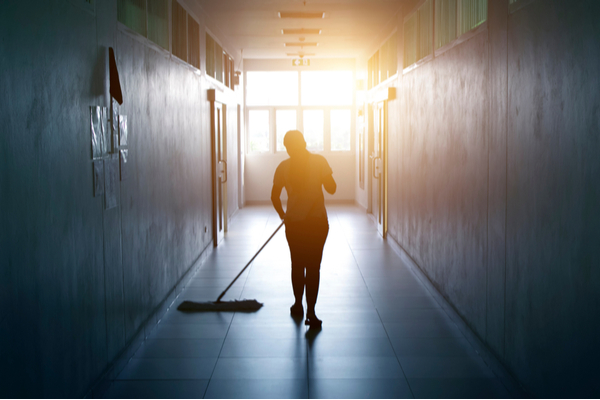 Janitor woman mopping floor in hallway office building