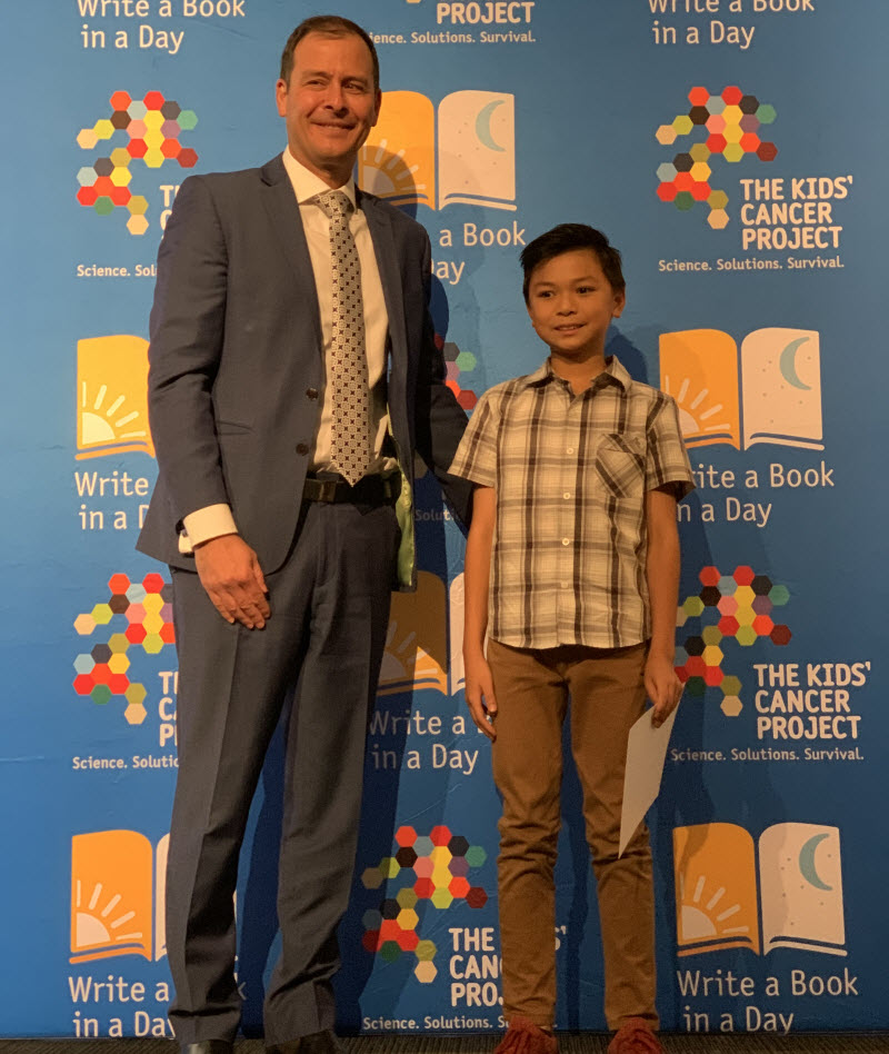 Man on suit standing beside a kid smiling at the camera