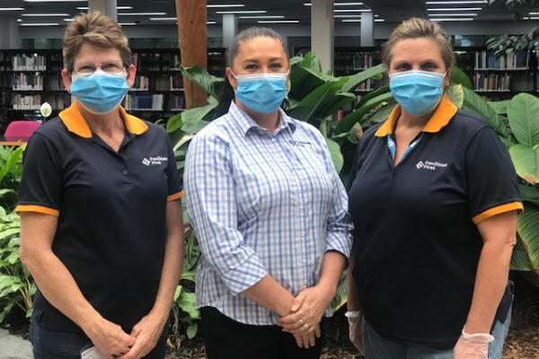 Three women wearing face masks in front of a library