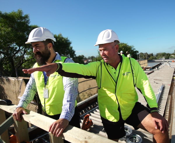 Men working on roof construction site | Facilities First