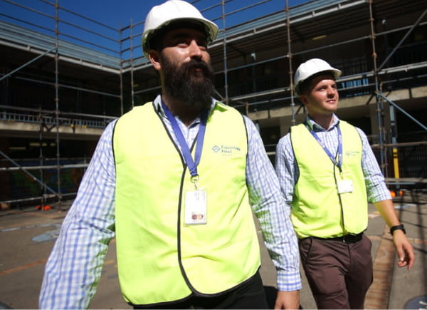 Two men walking at the construction site wearing a hard hat