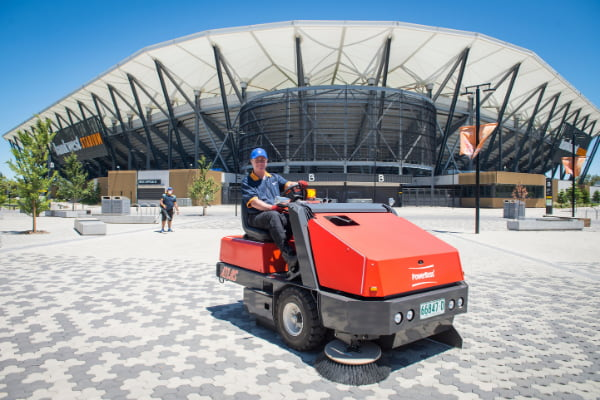 Man outside the stadium riding a cleaning equipment